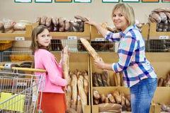 Madre e hija que eligen el pan en supermercado fotos de archivo libres de regalías