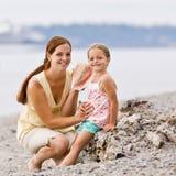 Madre e hija que escuchan el seashell en la playa fotos de archivo