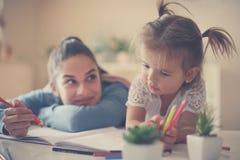 Madre e hija que gozan junto del libro de colorear Fotos de archivo