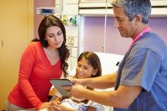 Madre e hija que hablan con el consultor In Hospital Room fotos de archivo libres de regalías