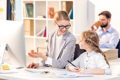Madre e hija que hablan en oficina de negocios, padre detrás imagen de archivo libre de regalías