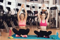 Madre e hija que hacen actitudes de la yoga en el gimnasio Parecen felices, de moda y aptos Fotos de archivo