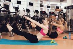 Madre e hija que hacen ejercicios aerobios en el gimnasio Parecen felices, de moda y aptos Imagenes de archivo