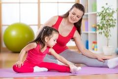 Madre e hija que hacen ejercicios de la aptitud en la estera en casa imagen de archivo