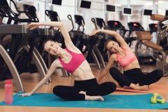 Madre e hija que hacen ejercicios de los pilates en el gimnasio Parecen felices, de moda y aptos Foto de archivo