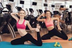 Madre e hija que hacen ejercicios de los pilates en el gimnasio Parecen felices, de moda y aptos Fotografía de archivo