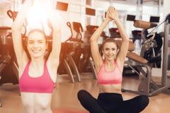 Madre e hija que hacen ejercicios de los pilates en el gimnasio Parecen felices, de moda y aptos Fotografía de archivo libre de regalías