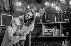 Madre e hija que hacen la preparación Mujer y adolescente que discuten el libro interesante Alumno que se prepara para la High Sc imagenes de archivo