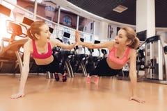 Madre e hija que hacen pectorales en piso en el gimnasio Parecen felices, de moda y aptos Fotografía de archivo libre de regalías