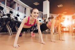 Madre e hija que hacen pectorales en piso en el gimnasio Parecen felices, de moda y aptos Fotos de archivo libres de regalías