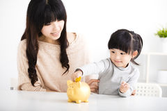 madre e hija que insertan la moneda en la hucha Fotografía de archivo