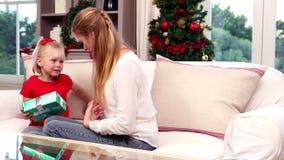 Madre e hija que intercambian los regalos en la Navidad almacen de metraje de vídeo