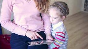 Madre e hija que juegan con la tableta electrónica metrajes