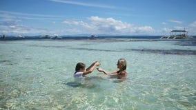 Madre e hija que juegan en el mar tropical almacen de metraje de vídeo