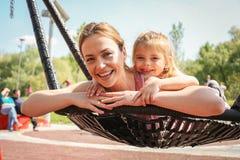 Madre e hija que juegan en el oscilación Imagen de archivo libre de regalías