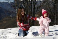 Madre e hija que juegan en la nieve Imagenes de archivo