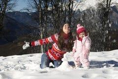 Madre e hija que juegan en la nieve Foto de archivo