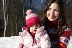 Madre e hija que juegan en la nieve Fotos de archivo libres de regalías