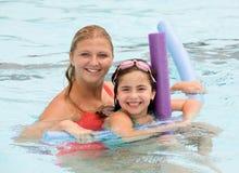 Madre e hija que juegan en la piscina Fotos de archivo libres de regalías