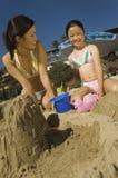 Madre e hija que juegan en la playa Fotos de archivo
