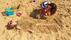 Madre e hija que juegan en la playa Fotos de archivo libres de regalías