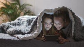 Madre e hija que juegan en panel táctil en cama almacen de video