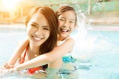 Madre e hija que juegan en piscina Fotografía de archivo libre de regalías