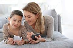 Madre e hija que juegan a juegos en smartphone Imágenes de archivo libres de regalías