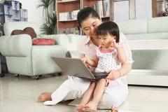 Madre e hija que juegan la computadora portátil junto Fotos de archivo libres de regalías