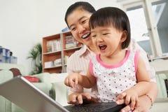 Madre e hija que juegan la computadora portátil junto Fotografía de archivo libre de regalías