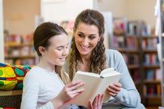 Madre e hija que leen un libro en biblioteca del centro de la comunidad fotos de archivo libres de regalías