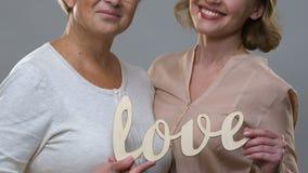 Madre e hija que llevan a cabo amor, gratitud y el cuidado de madera de la palabra para los padres almacen de metraje de vídeo