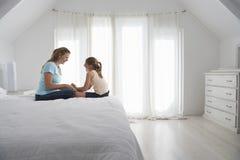 Madre e hija que llevan a cabo las manos en cama foto de archivo