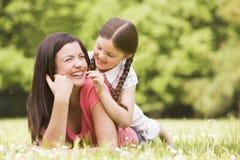 Madre e hija que mienten al aire libre con la flor Foto de archivo libre de regalías
