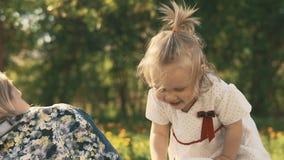 Madre e hija que mienten en el césped al aire libre Felicidad de la maternidad y de la niñez almacen de video