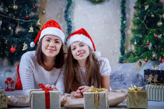 Madre e hija que mienten en sombreros de la Navidad Fotos de archivo
