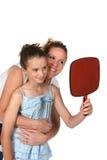 Madre e hija que miran en espejo Imágenes de archivo libres de regalías