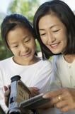 Madre e hija que miran la pantalla de la cámara de vídeo fotos de archivo
