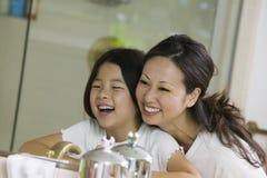 Madre e hija que miran la reflexión en espejo del cuarto de baño Fotografía de archivo libre de regalías