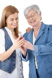 Madre e hija que miran las fotos en móvil Fotos de archivo