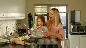 Madre e hija que preparan la comida en cocina almacen de metraje de vídeo