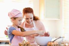 Madre e hija que preparan las galletas Foto de archivo