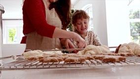 Madre e hija que preparan las galletas de la Navidad almacen de metraje de vídeo