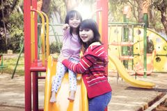 Madre e hija que presentan así como las diapositivas al aire libre Imagenes de archivo