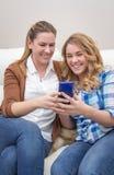 Madre e hija que ríen al mirar el teléfono Fotos de archivo libres de regalías