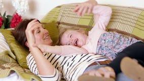 Madre e hija que ríen en el sofá almacen de video