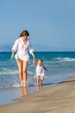 Madre e hija que recorren en la playa Imagen de archivo