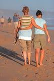 Madre e hija que recorren en la playa en la puesta del sol Imagen de archivo