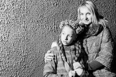 Madre e hija que se colocan cerca de la pared por la tarde Fotos de archivo libres de regalías