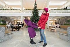 Madre e hija que se colocan cerca del árbol de navidad Foto de archivo libre de regalías